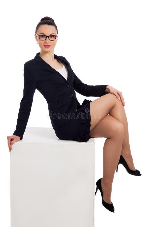 Mujer morena en falda negra y la chaqueta que se sientan en el cubo fotografía de archivo