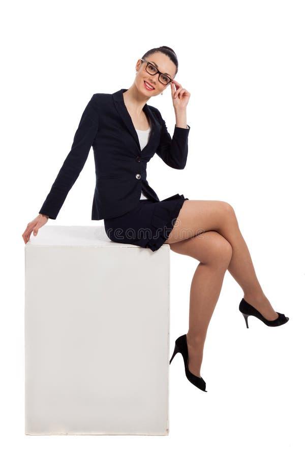 Mujer morena en falda negra y la chaqueta que se sientan en el cubo imagen de archivo