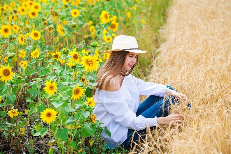 Mujer morena en la blusa blanca que se sienta en un fondo de los campos de oro del trigo y de los girasoles foto de archivo libre de regalías