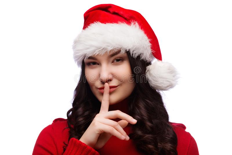 Mujer morena en sombrero de Navidad santa con el finger en los labios como concepto de silencio que ordena, aislado fotografía de archivo