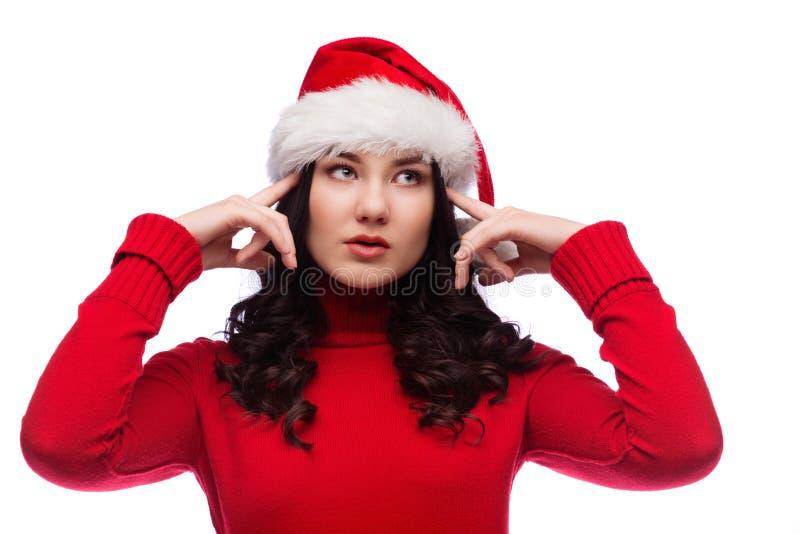 Mujer morena en uso del sombrero de la Navidad sus fingeres de señalar a la cabeza en el fondo blanco fotos de archivo libres de regalías