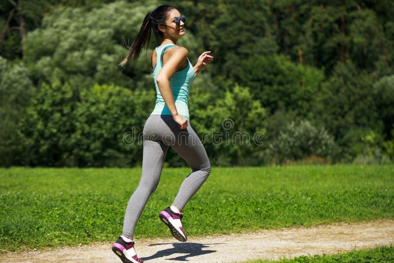 Mujer morena feliz atlética que se resuelve en un prado fotografía de archivo