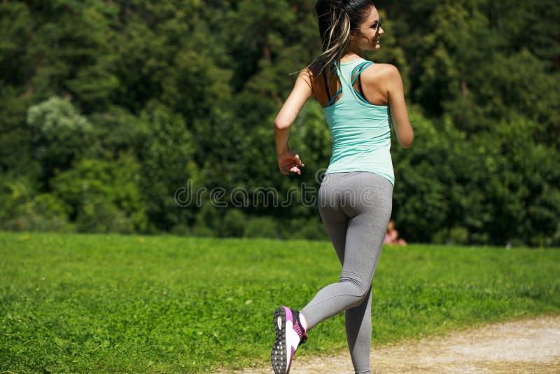 Mujer morena feliz atlética que se resuelve en un prado imagenes de archivo