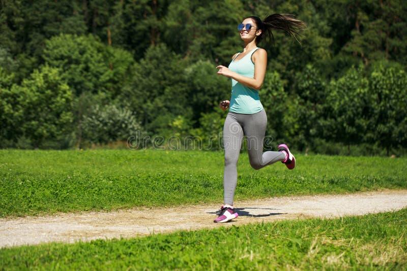 Mujer morena feliz atlética que se resuelve en un prado fotos de archivo