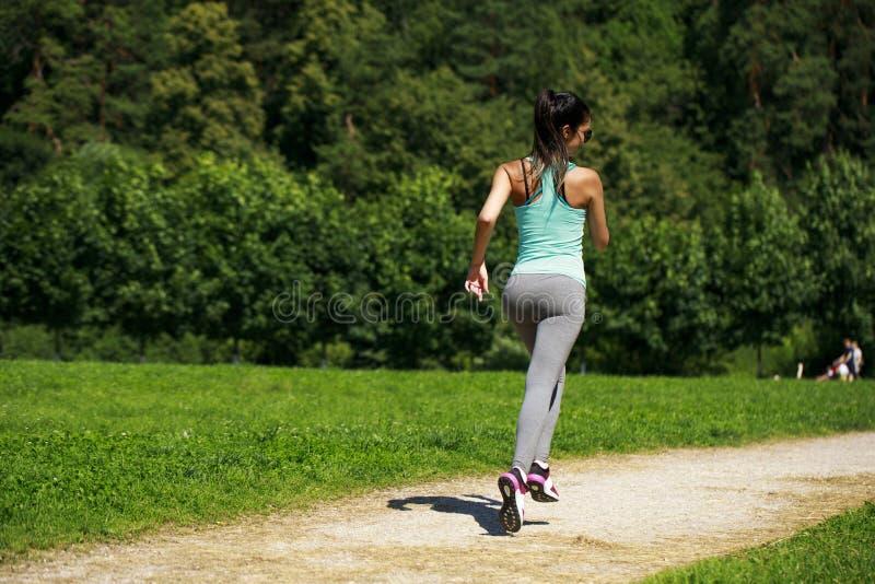 Mujer morena feliz atlética que se resuelve en un prado imágenes de archivo libres de regalías