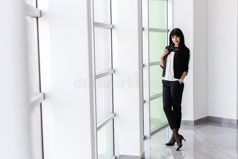 Mujer morena feliz atractiva joven vestida en una situación negra del traje de negocios cerca de la ventana en la oficina, sonris fotos de archivo libres de regalías