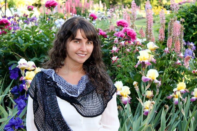 Mujer morena feliz en el ambiente de las flores fotografía de archivo libre de regalías