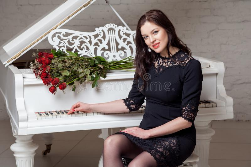 Mujer morena feliz hermosa en vestido clásico negro con el ramo de rosas rojas que se sientan en el piano y que miran la cámara c imagen de archivo