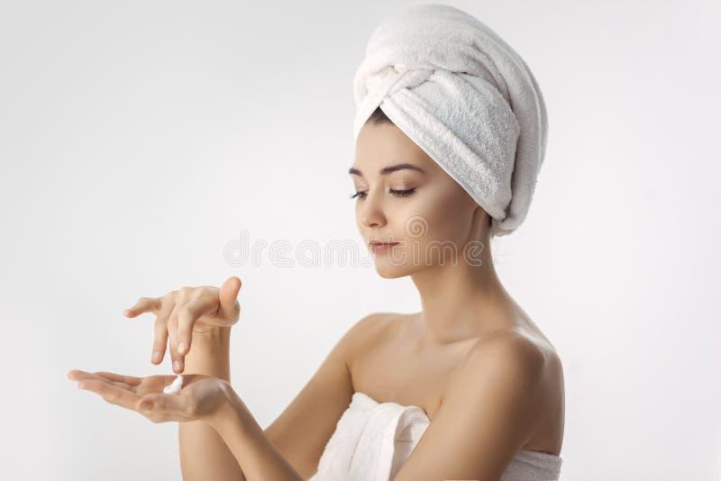 Mujer morena fresca y hermosa que aplica la crema de las manos foto de archivo