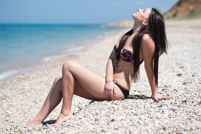 Mujer morena hermosa en la playa foto de archivo