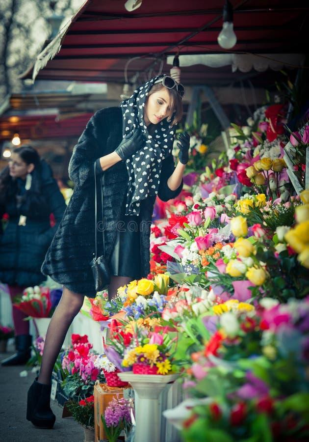 Mujer morena hermosa en negro en la floristería fotos de archivo libres de regalías