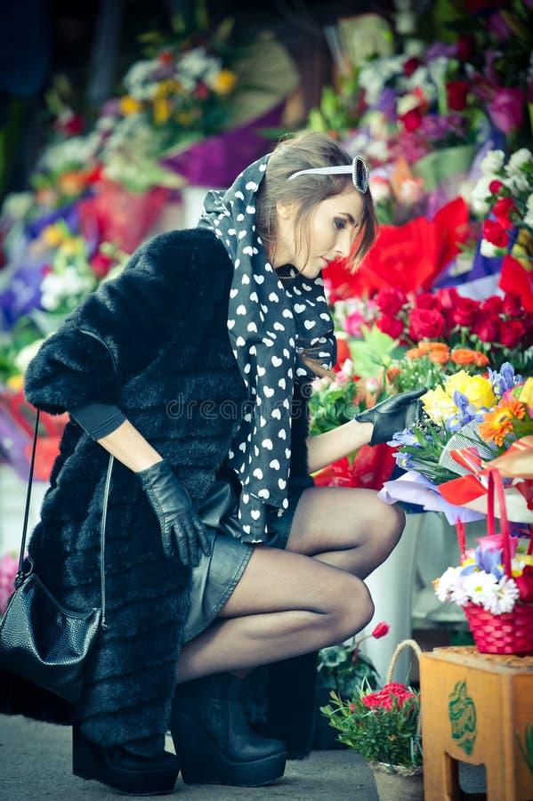 Mujer morena hermosa en negro en la floristería imagenes de archivo