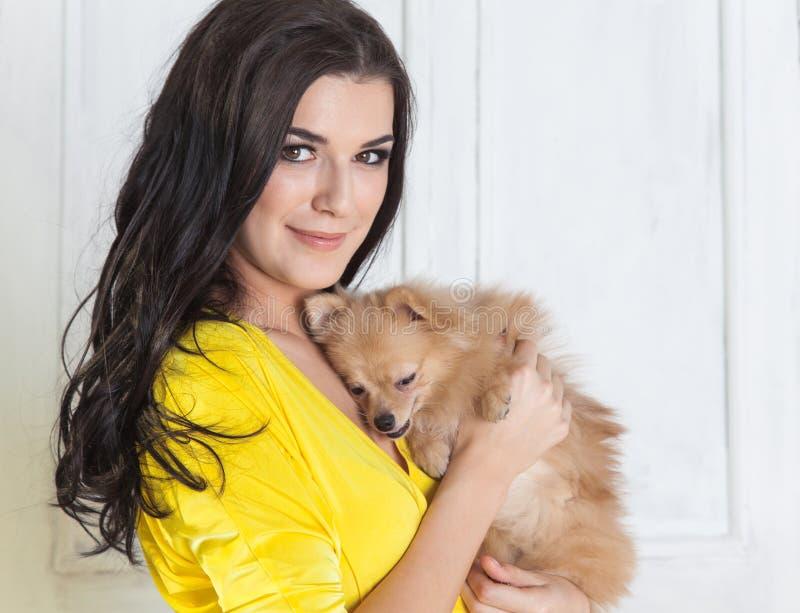 Mujer morena hermosa en vestido amarillo con el pequeño perro en manos foto de archivo