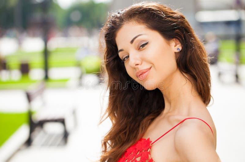 Mujer morena hermosa en vestido rojo atractivo imagen de archivo libre de regalías