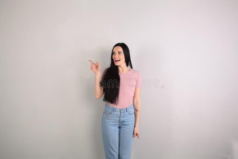 Mujer morena hermosa joven con el pelo largo que hace una pausa los vaqueros que llevan del fondo gris y la camisa rosada sorpren fotografía de archivo