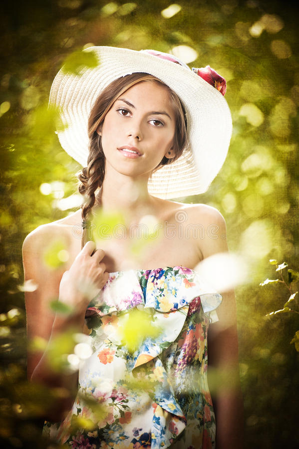 Mujer morena hermosa joven que lleva un sombrero grande en un día soleado fotos de archivo libres de regalías
