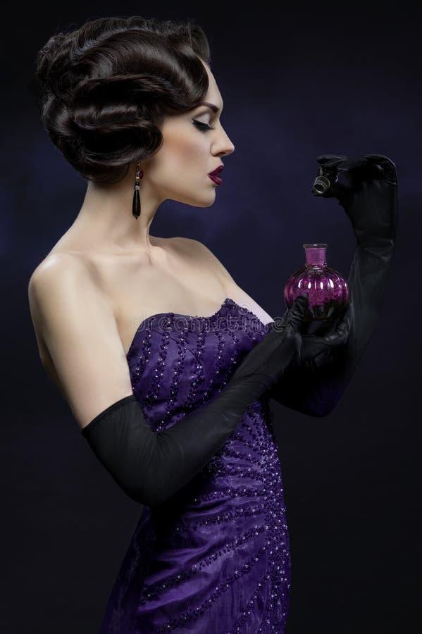 Mujer morena hermosa joven que presenta con la botella de perfume imagen de archivo libre de regalías