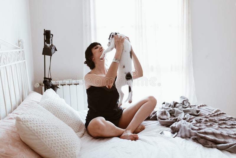 Mujer morena hermosa que abraza su perrito dulce de Labrador en dormitorio foto de archivo libre de regalías