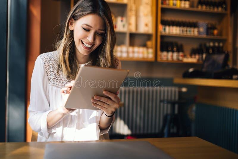 Mujer morena hermosa que usa el ordenador portátil en café foto de archivo