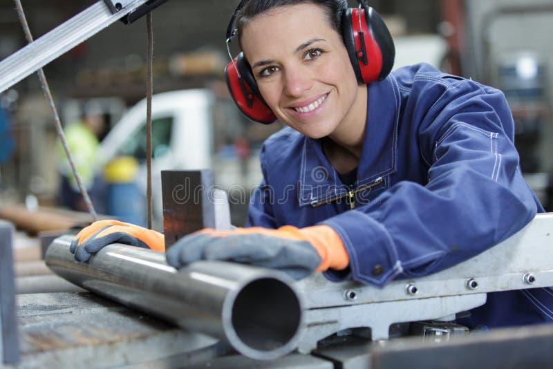 Mujer morena hermosa sonriente en fábrica fotos de archivo