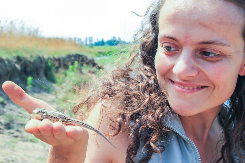 Mujer morena joven atractiva con el pelo enorme rizado que sonríe y que sostiene un lagarto imagen de archivo