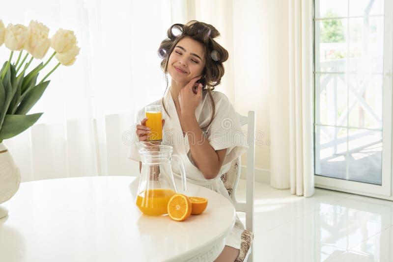 Mujer morena joven atractiva en bigudíes de pelo que goza del jugo exprimido fresco anaranjado que se sienta en la cocina brillan imagen de archivo libre de regalías