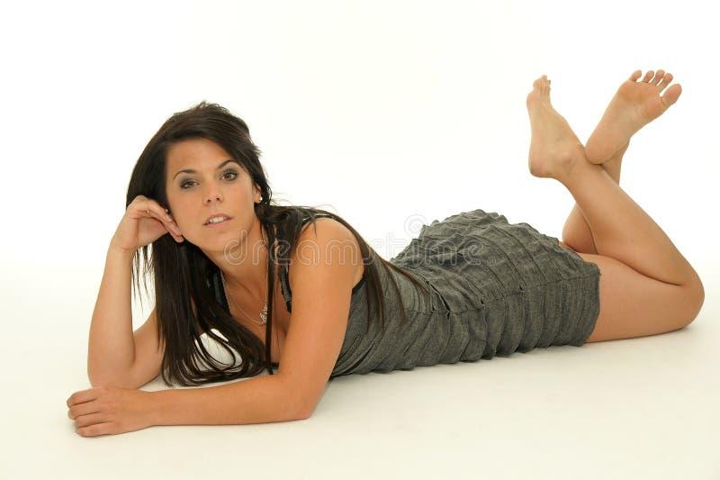 Mujer morena joven atractiva en el piso fotografía de archivo
