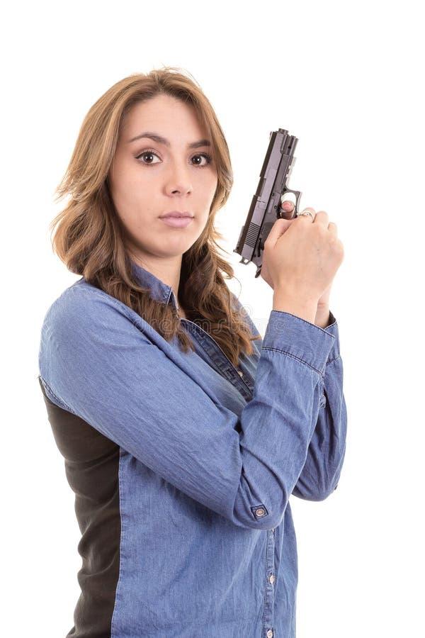 Mujer morena joven con el arma aislado en blanco fotos de archivo