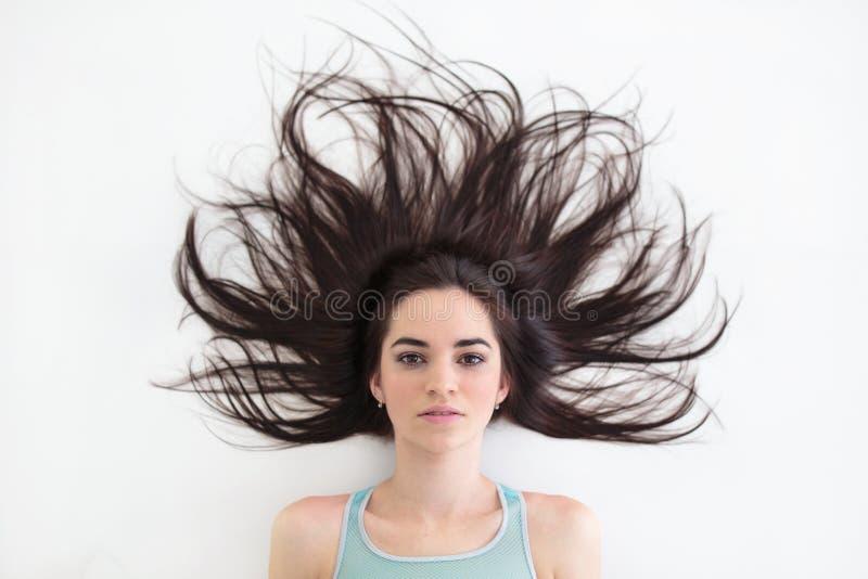 Mujer morena joven con el peinado bonito que miente en el piso foto de archivo