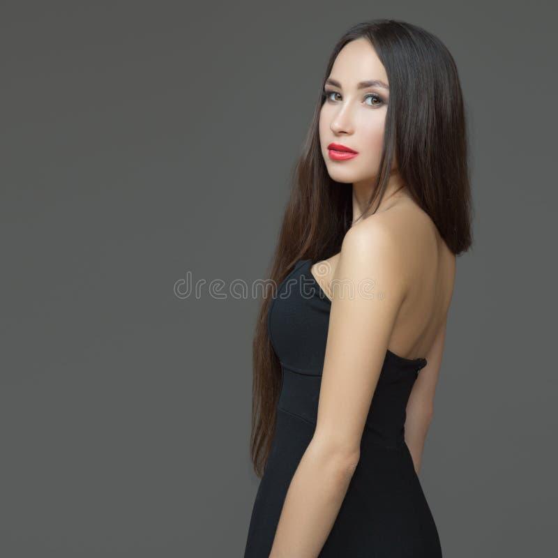 Mujer morena joven con la barra de labios roja y el pelo recto largo Vestido abierto negro imágenes de archivo libres de regalías