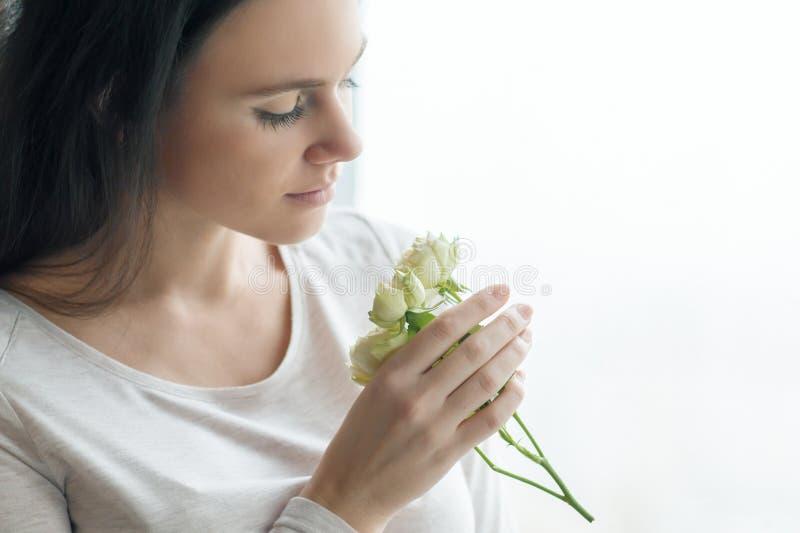 Mujer morena joven con las flores color de rosa blancas, muchacha cerca de la ventana con las gotas de agua fotografía de archivo libre de regalías