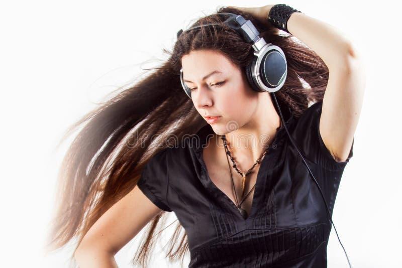 Mujer morena joven en auriculares grandes que escucha la m?sica y que se divierte foto de archivo libre de regalías