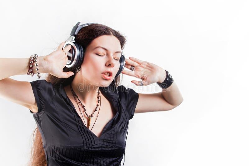 Mujer morena joven en auriculares grandes que escucha la m?sica y que se divierte foto de archivo