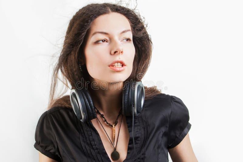 Mujer morena joven en auriculares grandes que escucha la m?sica y que se divierte imagen de archivo