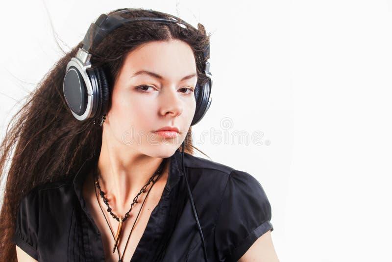 Mujer morena joven en auriculares grandes que escucha la m?sica y que se divierte imagenes de archivo