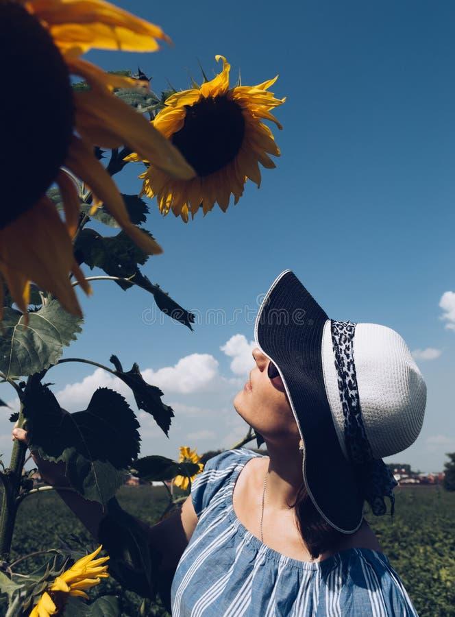 Mujer morena joven en el sombrero que mira el girasol floreciente imagen de archivo libre de regalías