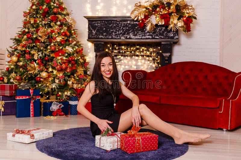 Mujer morena joven en el vestido negro corto que se sienta en la alfombra cerca del árbol de navidad Mujer joven de risa Hembra h foto de archivo