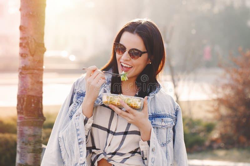 Mujer morena joven en gafas de sol que come la ensalada fresca al aire libre imagenes de archivo