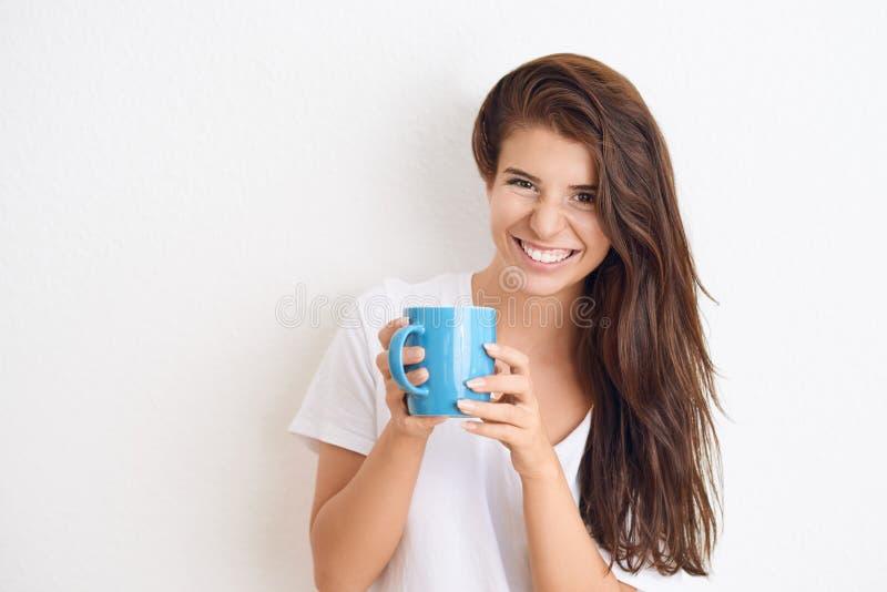 Mujer morena joven en la camiseta blanca que bebe de la taza azul fotografía de archivo libre de regalías
