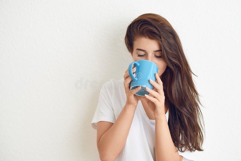 Mujer morena joven en la camiseta blanca que bebe de la taza azul imagen de archivo libre de regalías