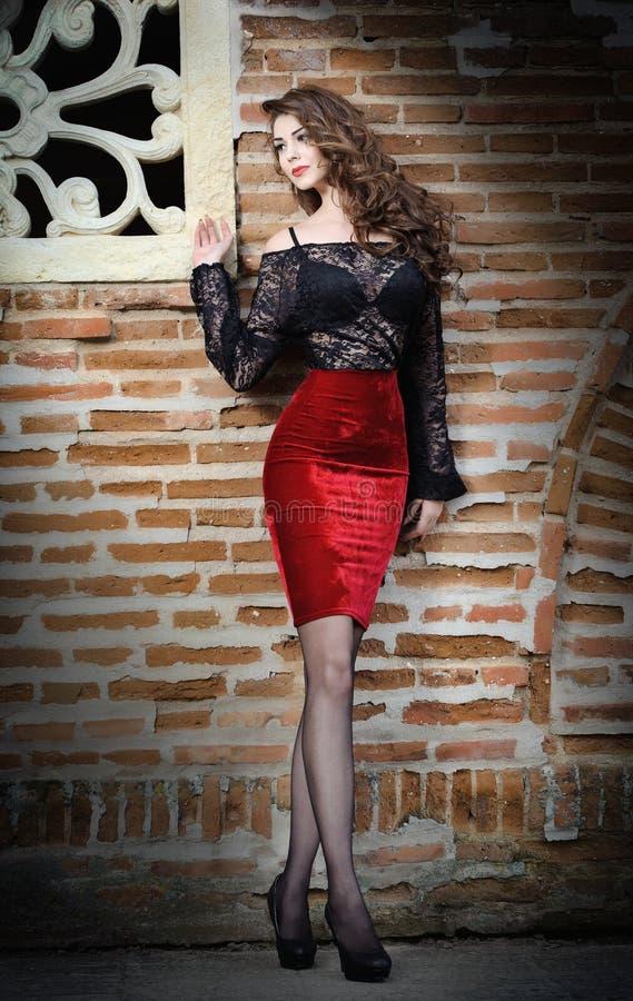 Mujer morena joven encantadora en blusa negra del cordón, falda roja y tacones altos cerca de la pared de ladrillo. Mujer joven ma imagen de archivo libre de regalías