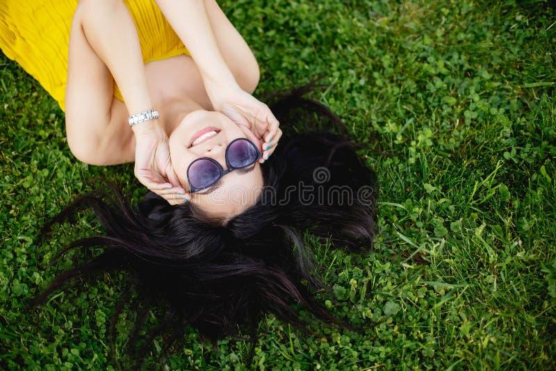 Mujer morena joven feliz en las gafas de sol que mienten en la hierba, visión superior imagen de archivo