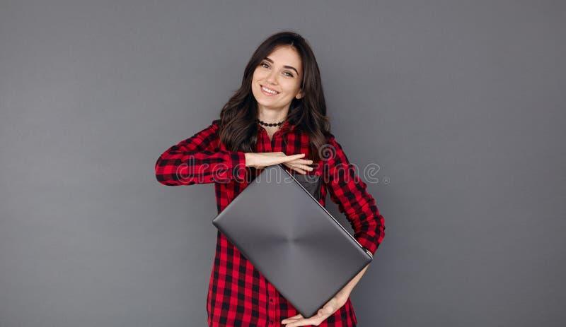 Mujer morena joven feliz que sostiene un ordenador portátil fotos de archivo libres de regalías