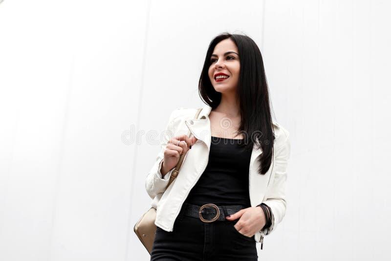 Mujer morena joven hermosa bonita con los labios rojos en una sonrisa atractiva en una chaqueta blanca de moda en una camiseta foto de archivo libre de regalías