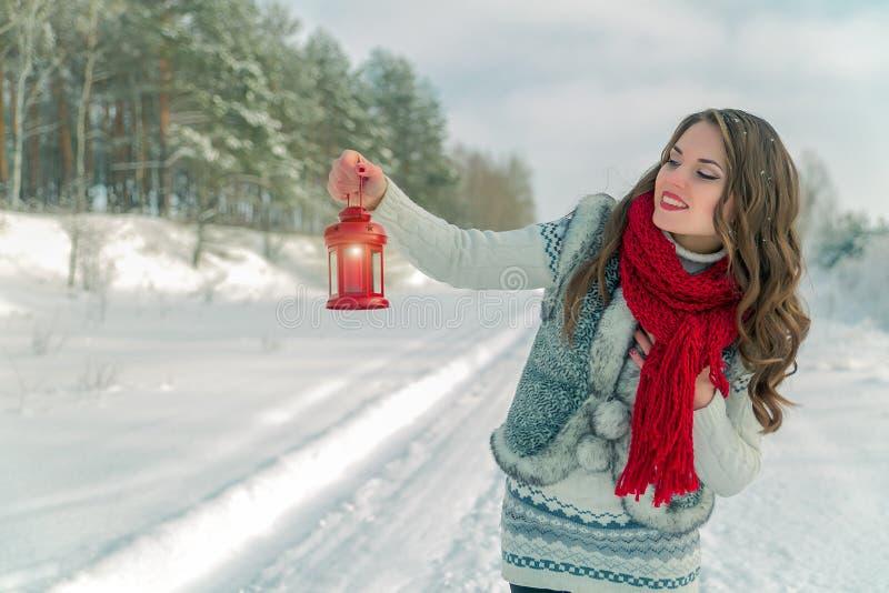 Mujer morena joven hermosa en la bufanda que sostiene la linterna roja de la Navidad con una vela fotografía de archivo libre de regalías