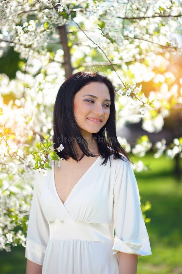 Mujer morena joven hermosa en una risa del parque de la primavera fotos de archivo