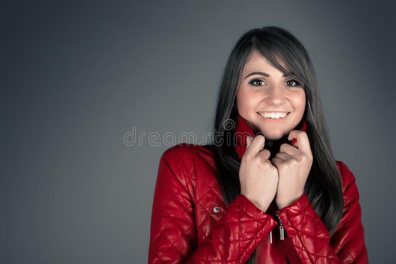 Mujer morena joven hermosa que lleva la chaqueta de cuero roja fotos de archivo