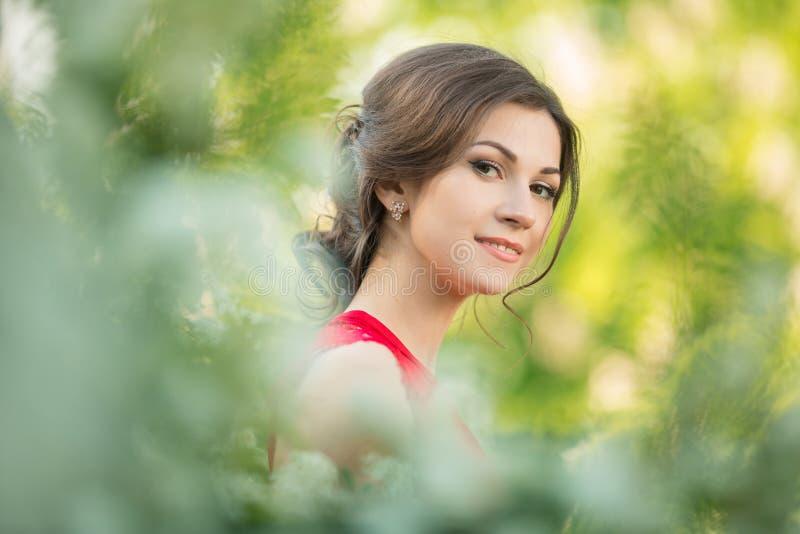 Mujer morena joven hermosa que se coloca cerca del flor blanco imagen de archivo