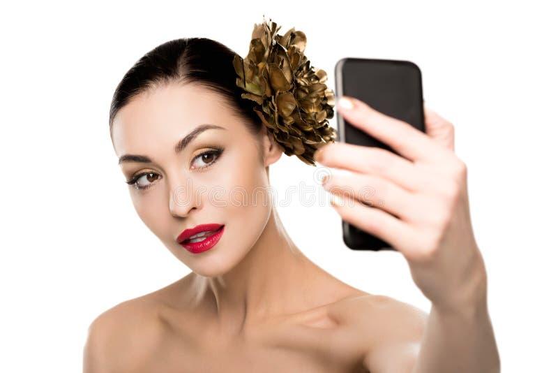 Mujer morena joven magnífica con la flor de oro en el pelo que toma el selfie en smartphone imágenes de archivo libres de regalías