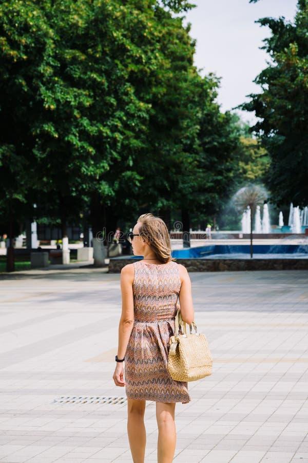 Mujer morena joven que camina en parque contra de la fuente foto de archivo